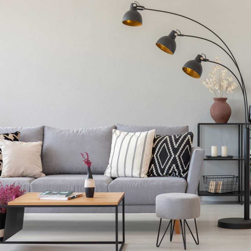 Black industrial lamp next to gray couch with patterned pillows, coffee table and pouf in monochromatic living room