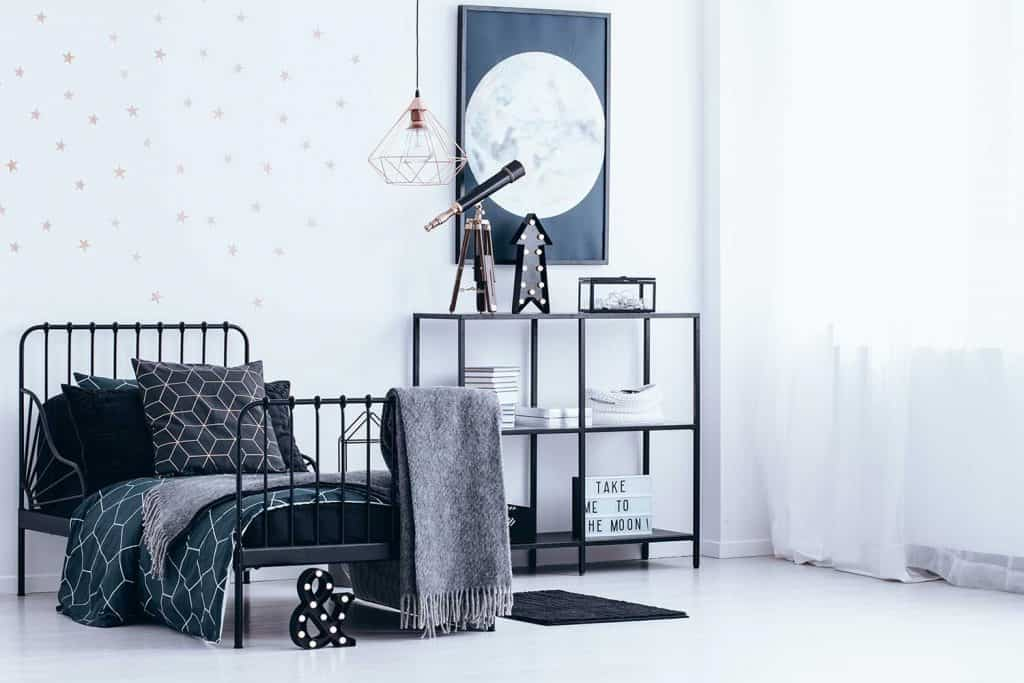 Blanket on black bed with dark bedsheets against the wall with gold stars next to shelf with telescope in bedroom interior