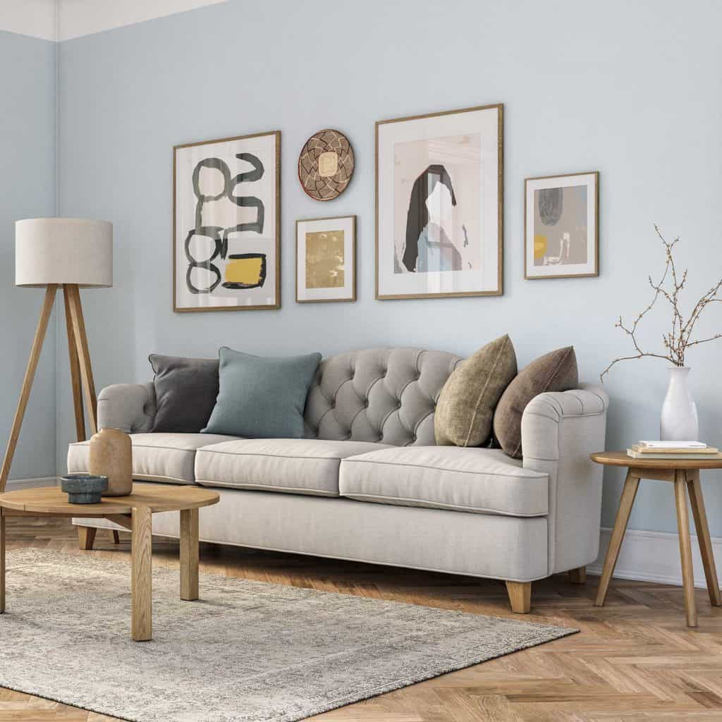 Bohemian living room interior with beige colored furniture, wooden elements and light blue colored wall