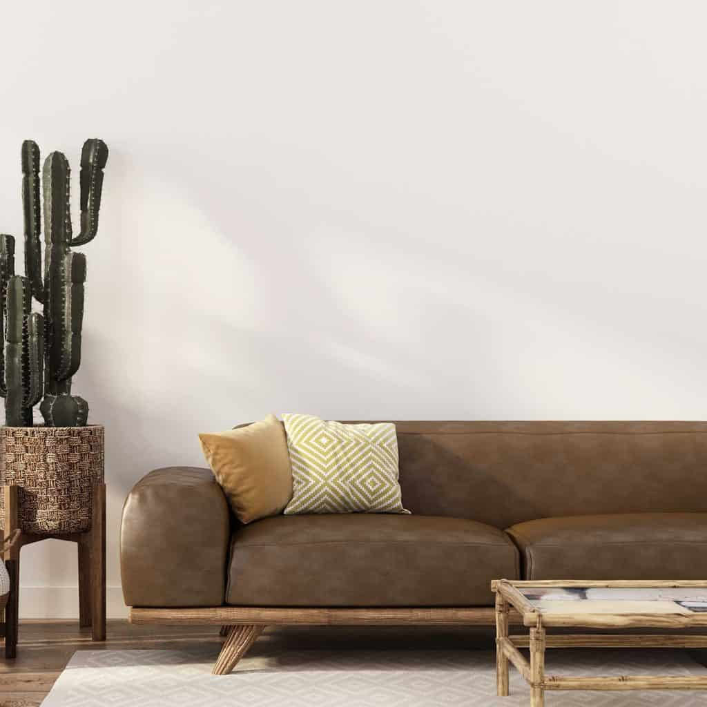Boho-style interior with stylish leather sofa, rattan table and wicker pots with cacti