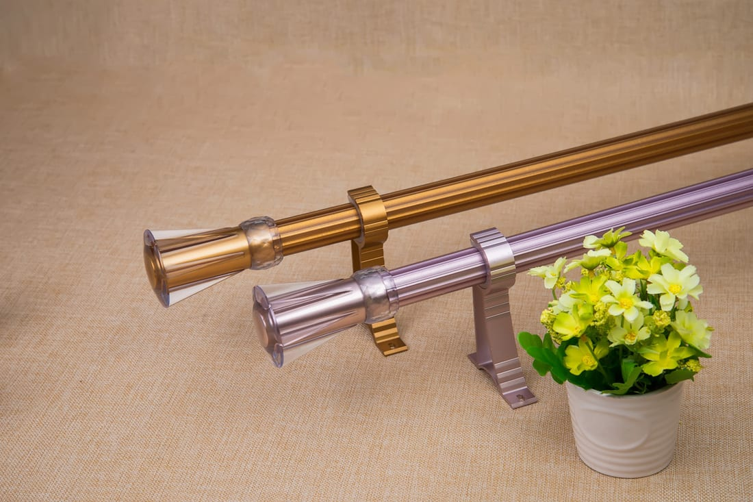 Brass and silver curtain rods placed on the floor with a small flower vase on the side, How To Choose Curtain Rods [You MUST check these 3 things]