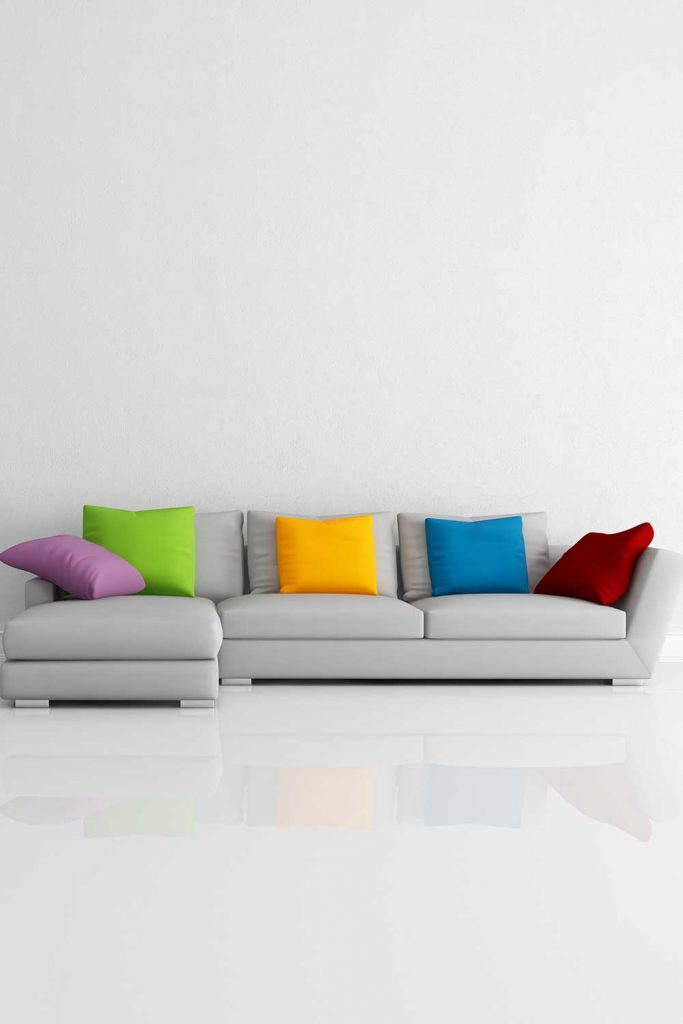 Bright colored minimalist living room with cozy light grey sofa