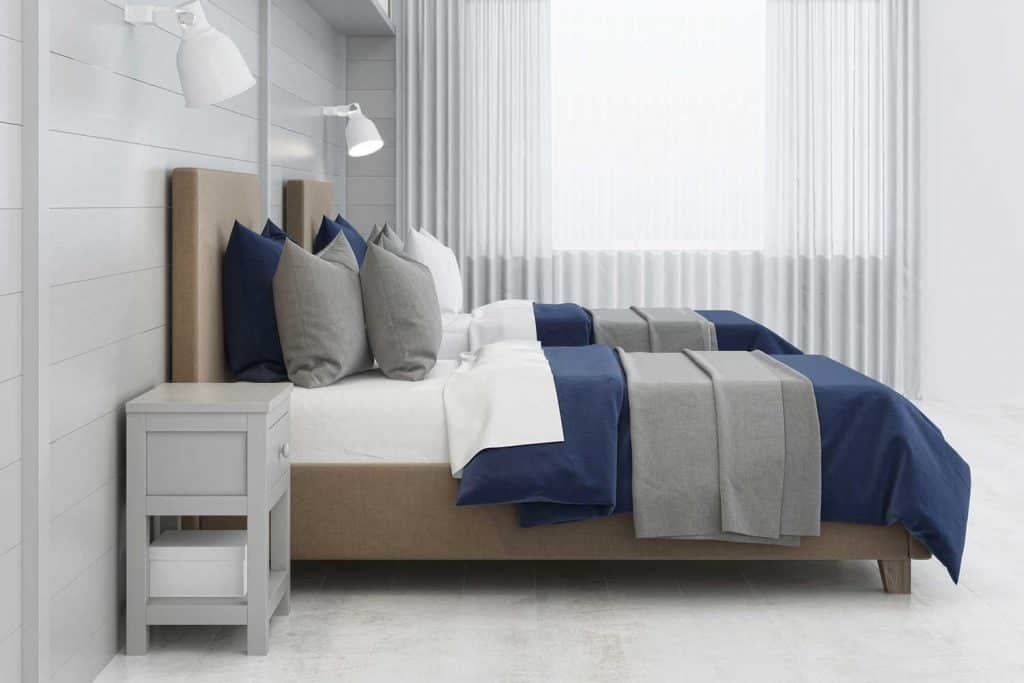 Children's room with two bed, wall lights, gray wooden wall and window