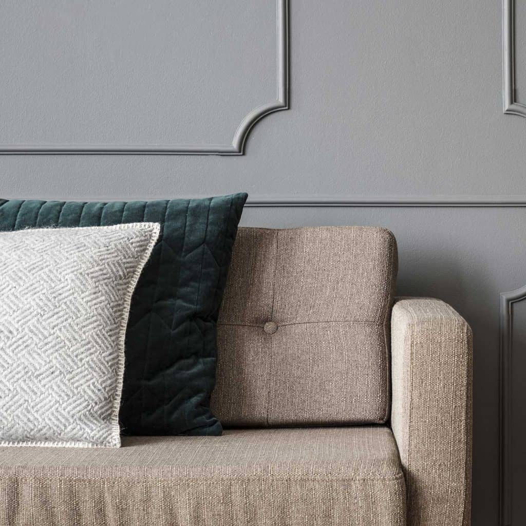 Close-up of pillows on beige sofa against grey wall with molding in living room interior