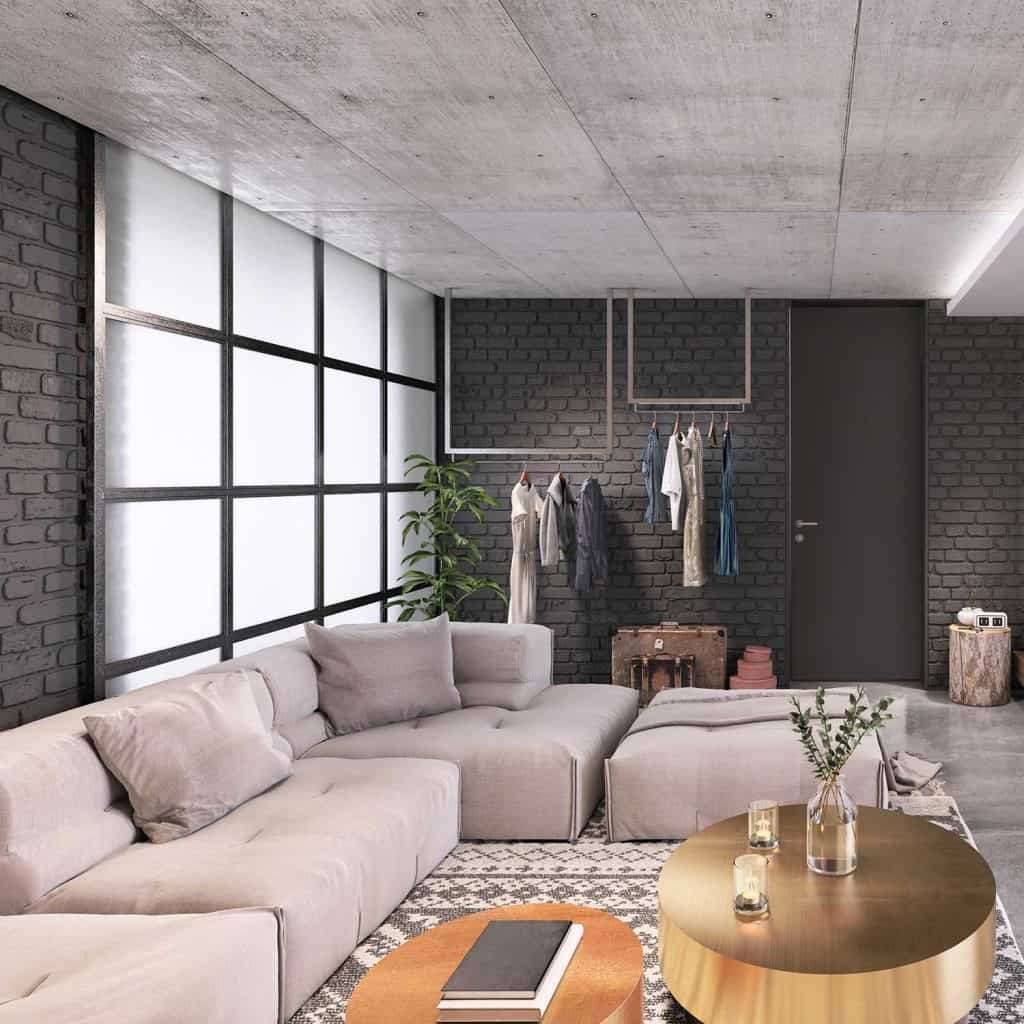 Clothes rack, large corner sofa and coffee table in modern studio loft apartment living room with dark gray brick wall