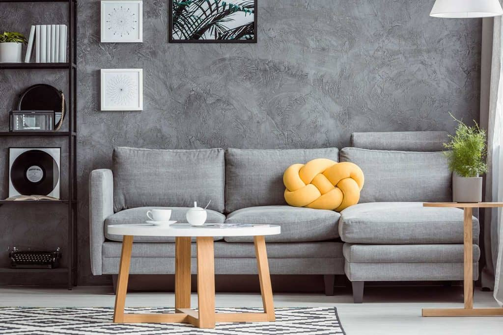 Contemporary design of cozy grey living room interior with simple sofa, coffee table, rack, plant and yellow cushion