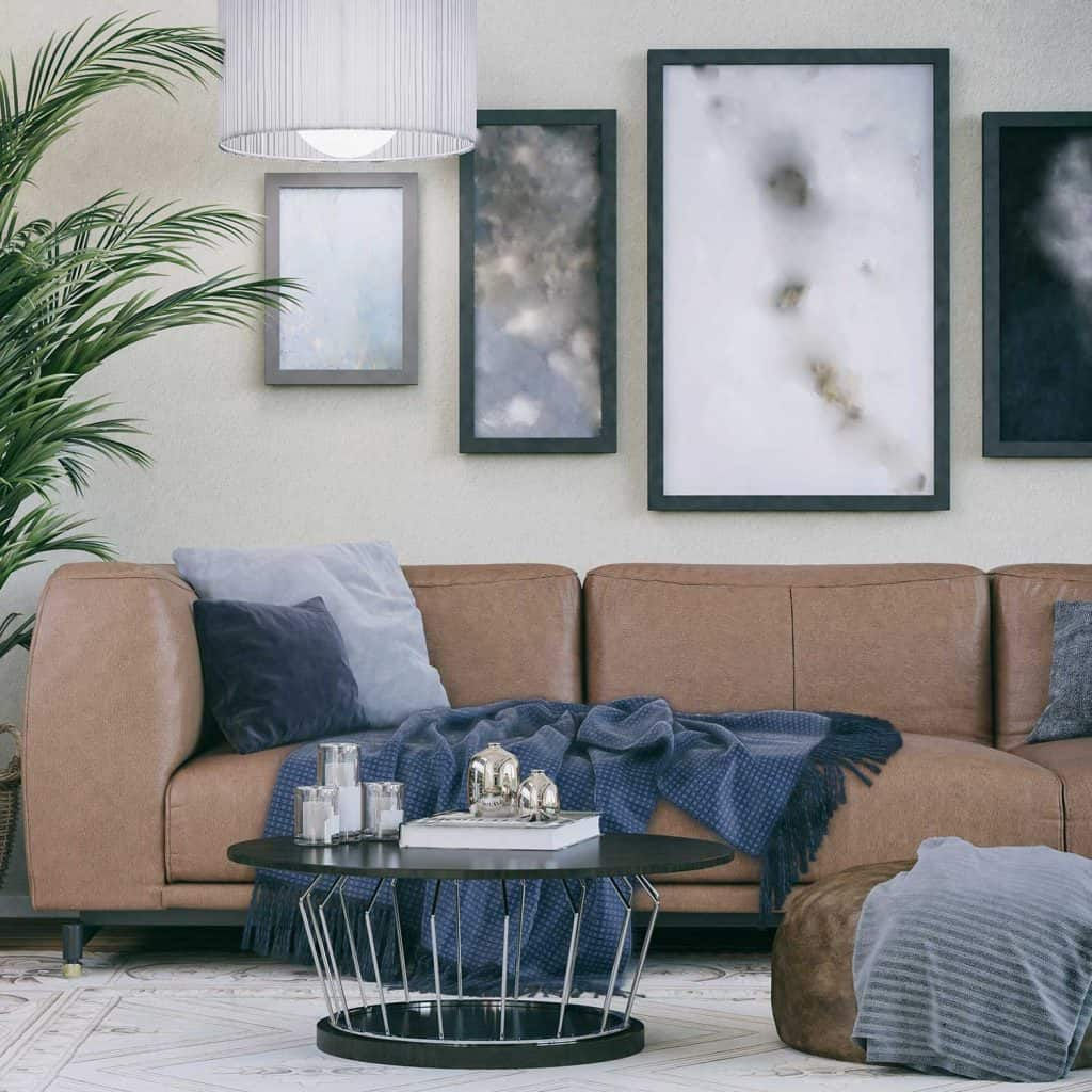 Cozy brown leather sofa in domestic living room with framed wall decor, house plant and coffee table