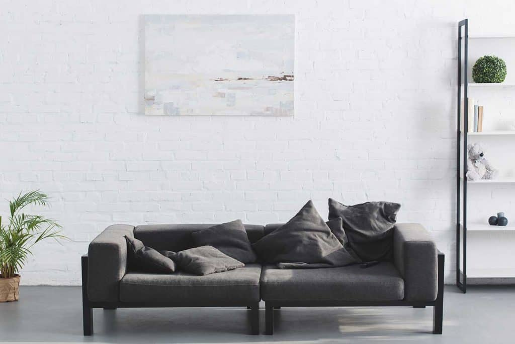 Cozy gray sofa in modern living room interior with painting on white brick walls