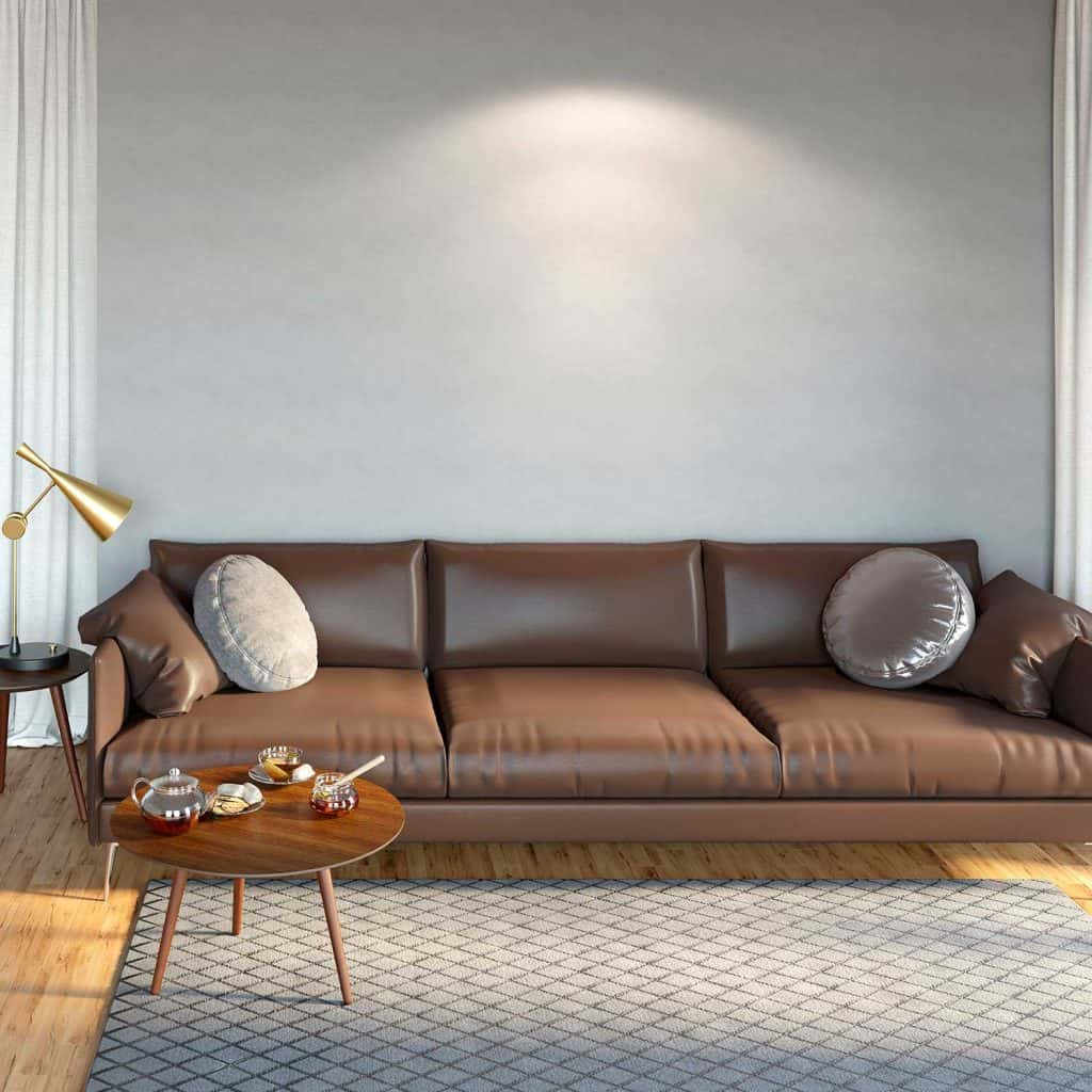 Cozy room interior with a brown leather sofa, a coffee table with a teapot and honey