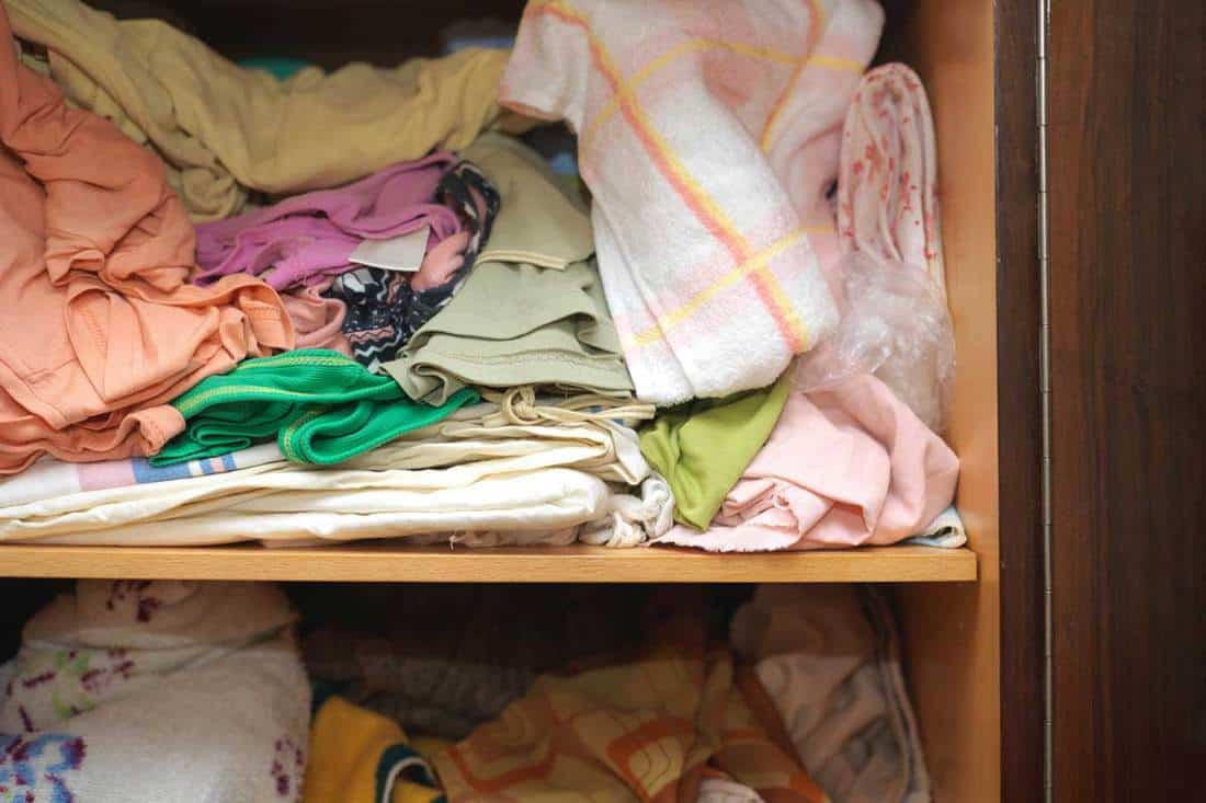 Crumpled linen and towels on a shelf of closet in complete mess, indoors close-up