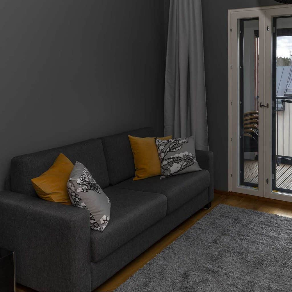 Dark gray sofa and throw pillows in scandinavian minimalistic guest bedroom