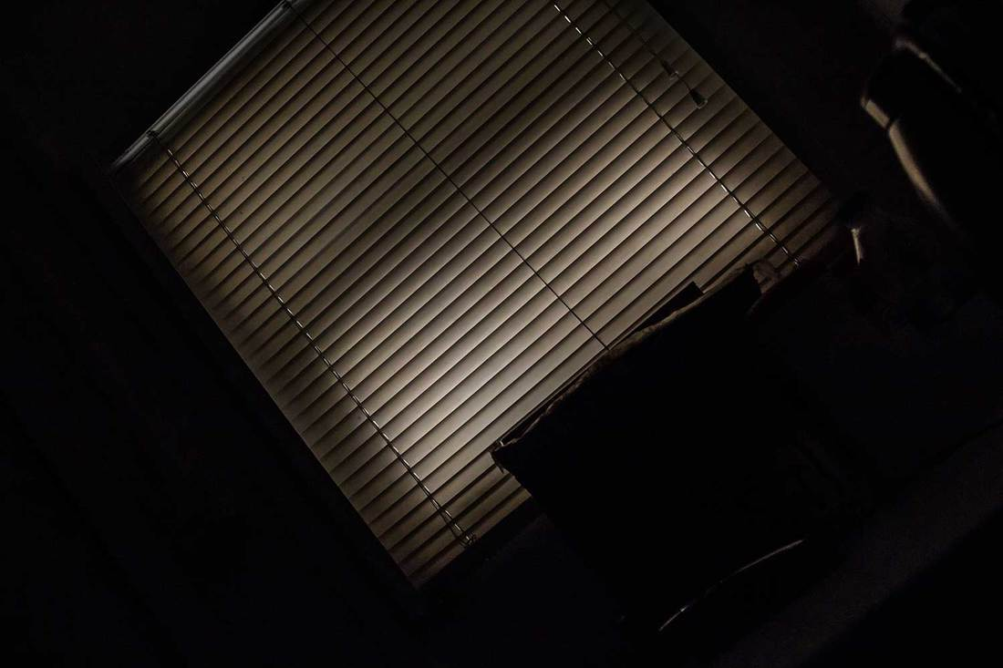 Dark room with closed off-white Venetian blinds