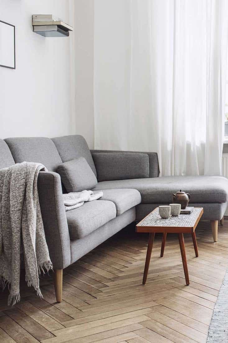 Design interior of living room with small design table and grey sofa