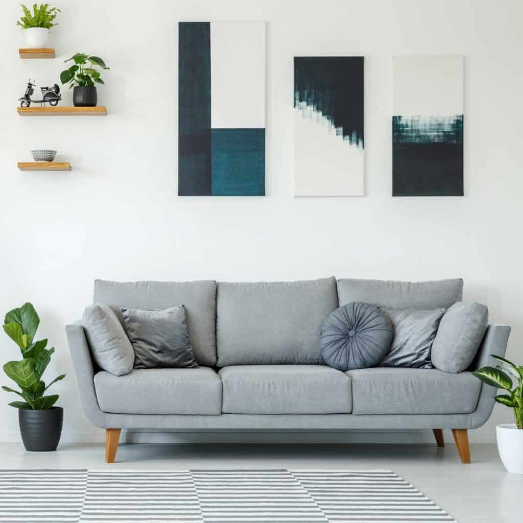 Elegant living room interior with grey sofa, plants and paintings on the wall