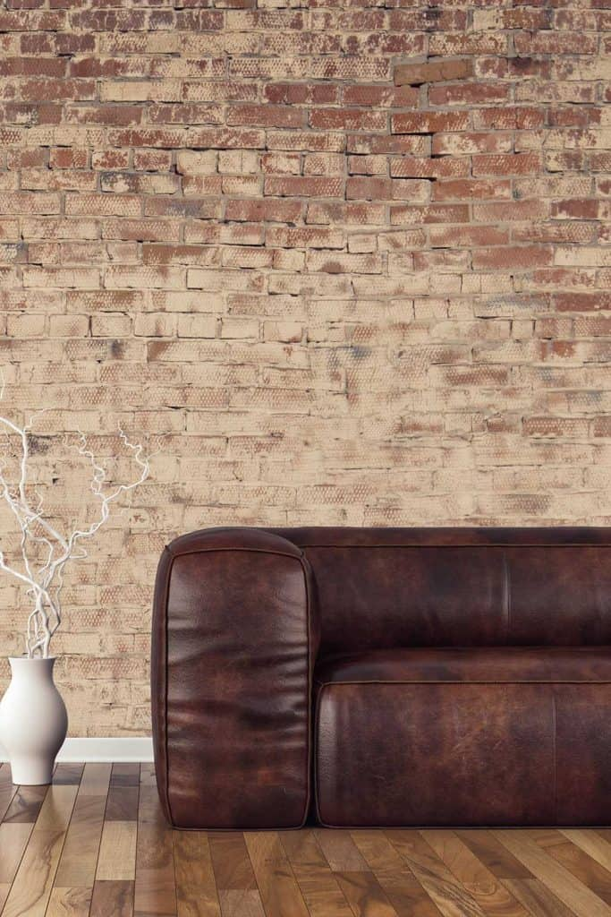 Empty living room with brown leather sofa on hardwood floor in front of ruined brick wall