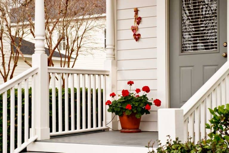 Front porch of a traditional American home with geraniums, What Color Should I Paint My Front Porch?