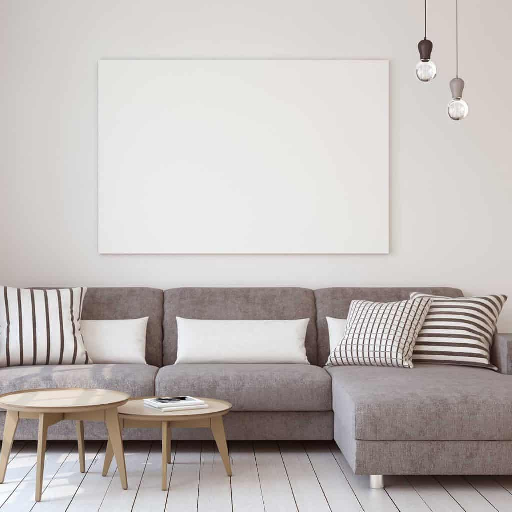 Grey corner sofa with throw pillows and coffee tables in wooden floor apartment living room