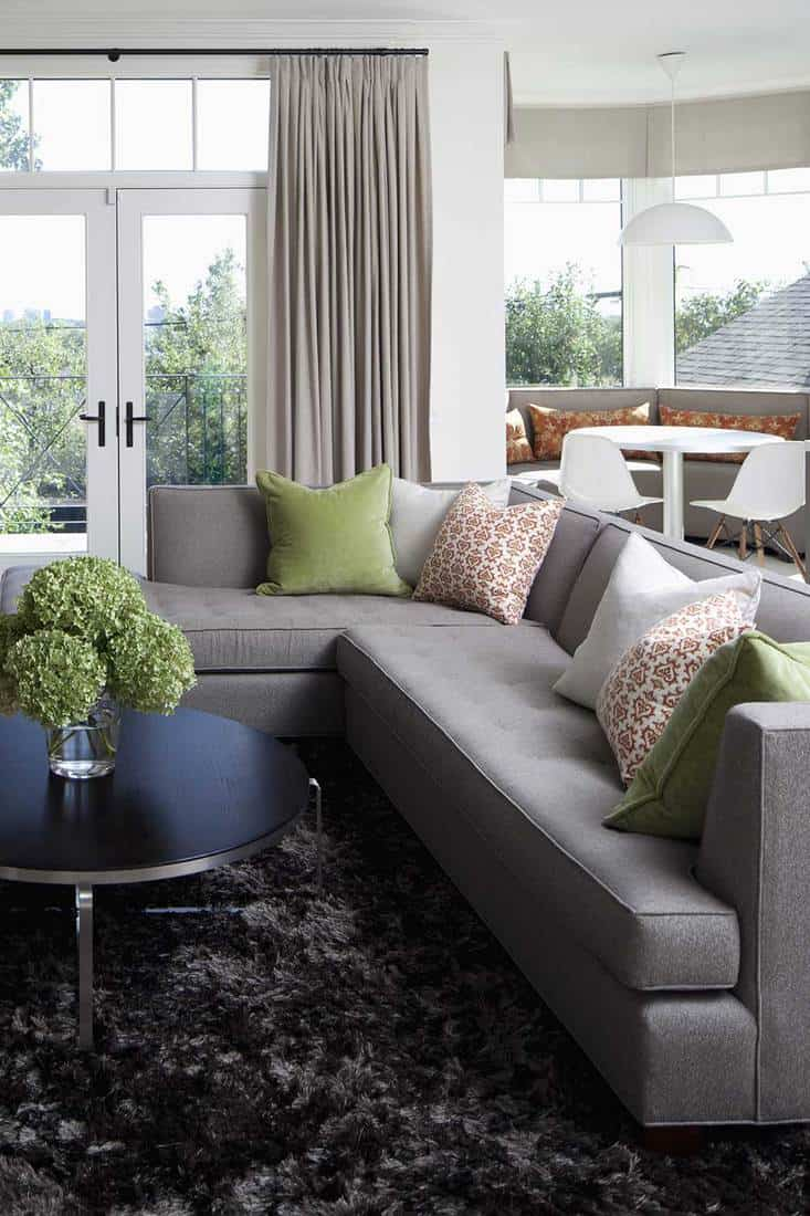 Grey corner sofa with throw pillows and round coffee table with house plants