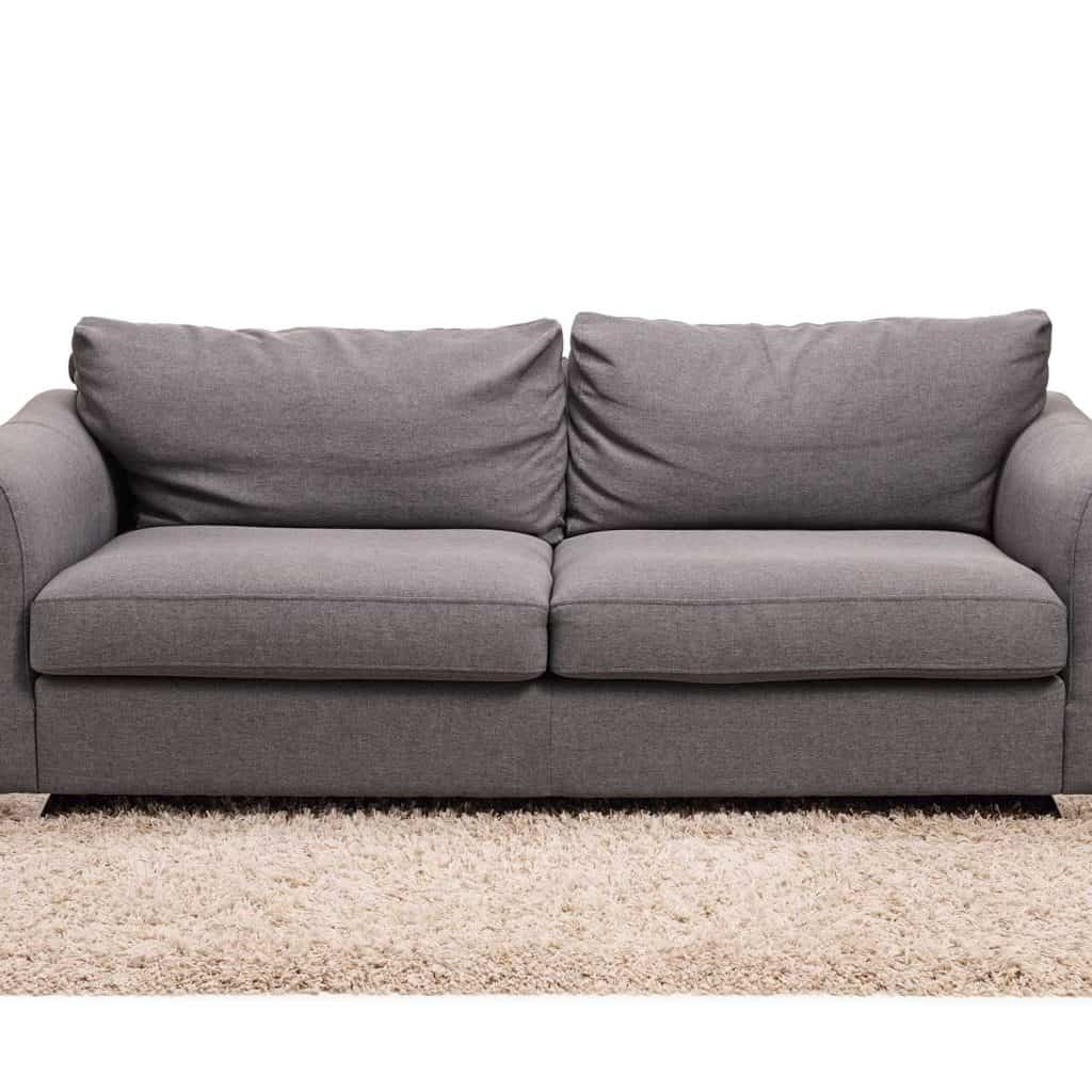 Grey sofa on a carpet isolated on white background