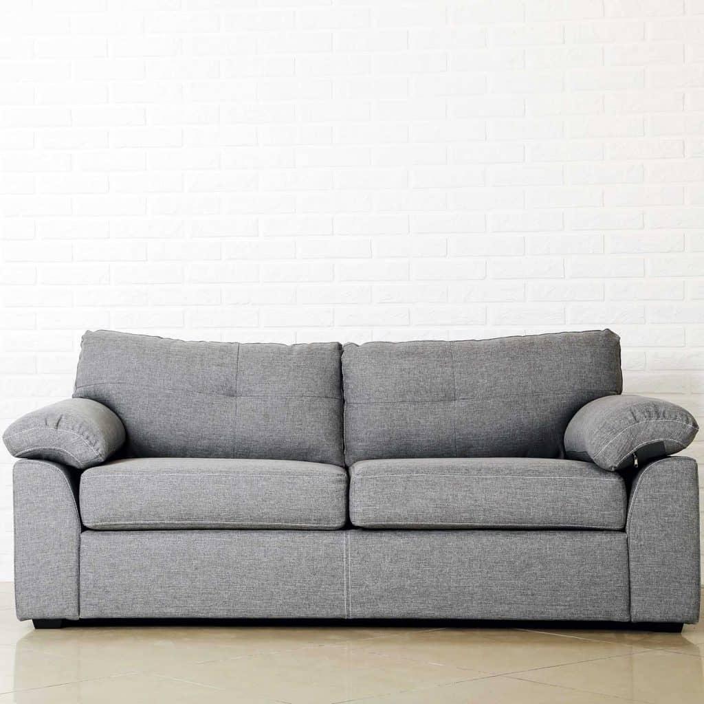 Grey sofa on a white brick wall background