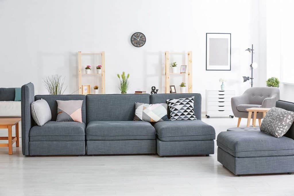 Gray sofa with different pillows, accent chair, wall clock and white cabinet in modern living room