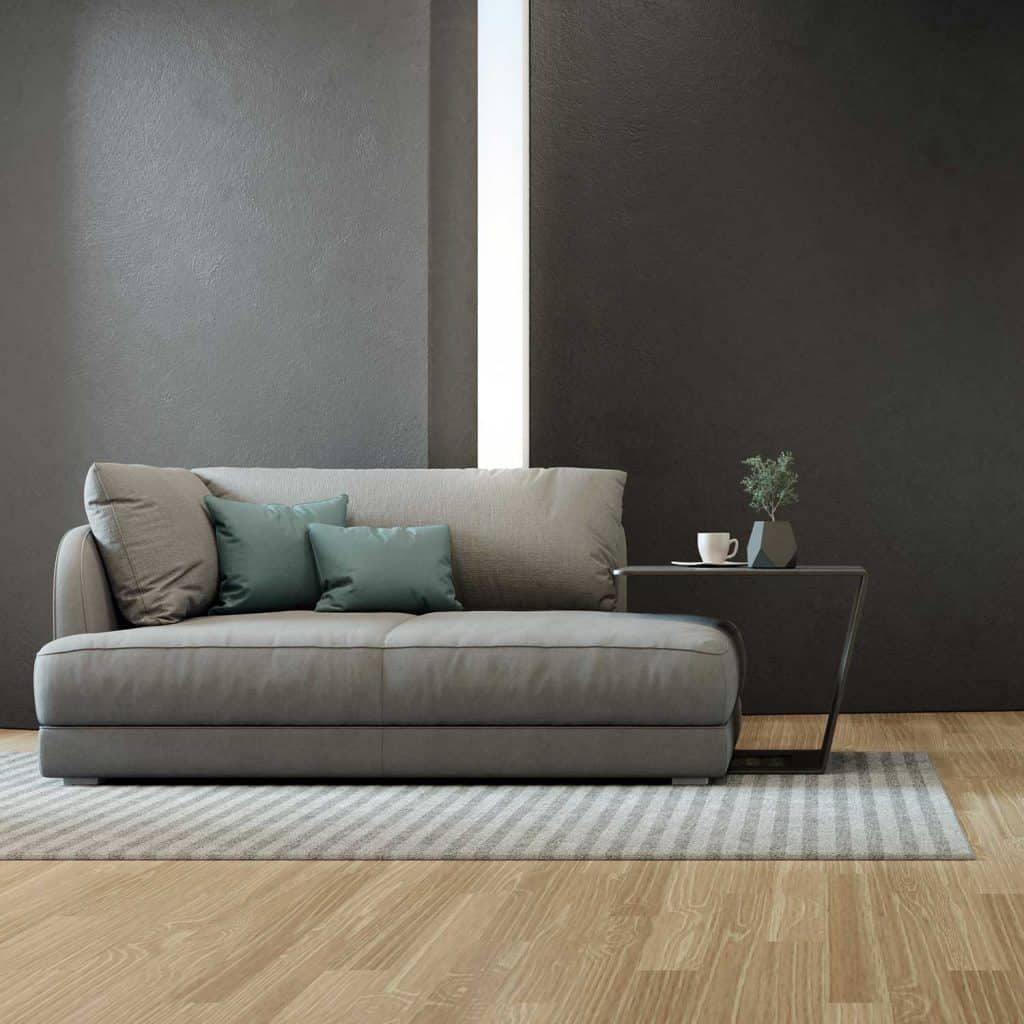 Gray sofa with throw pillow, parquet floor and black concrete wall background in a vacation home