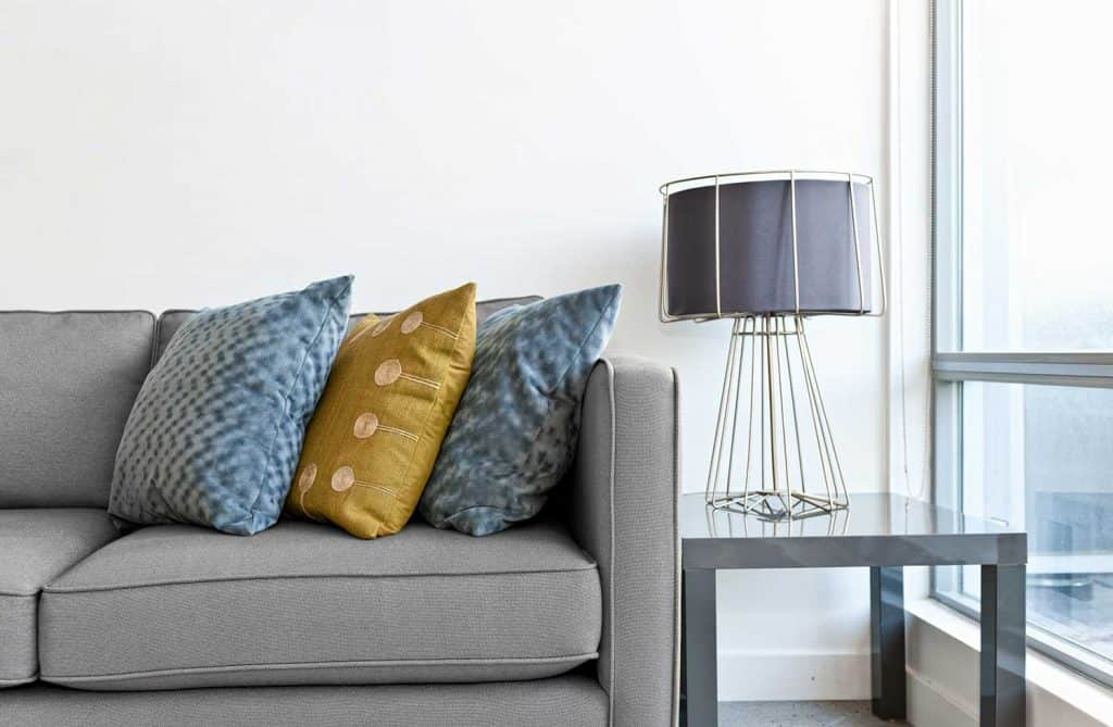 Gray sofa with throw pillows and side table with lamp