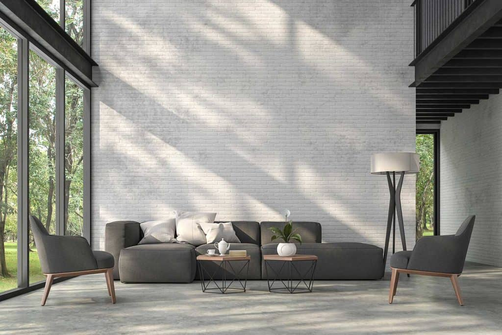 High ceiling loft living room with nature view glass window, white brick wall, polished concrete floor, dark gray sofa, accent chairs and coffee tables