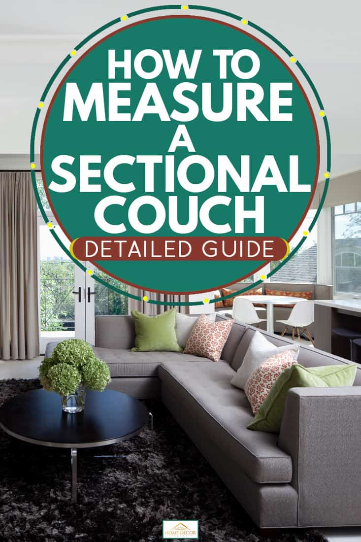 A modern living room with a gray sectional sofa and a wall mounted TV next to a gray colored divider set, How To Measure A Sectional Couch [Detailed Guide]
