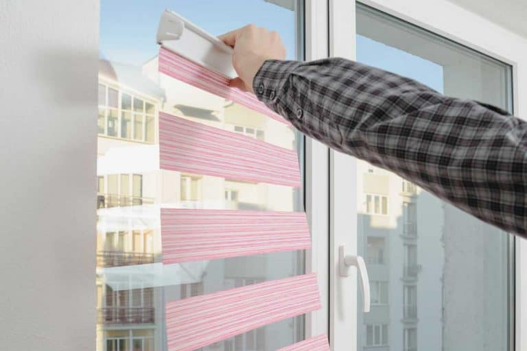 Installing pink fabric roller blinds on glass window with city view, How To Hang Blinds Without Drilling Holes [4 EASY methods]