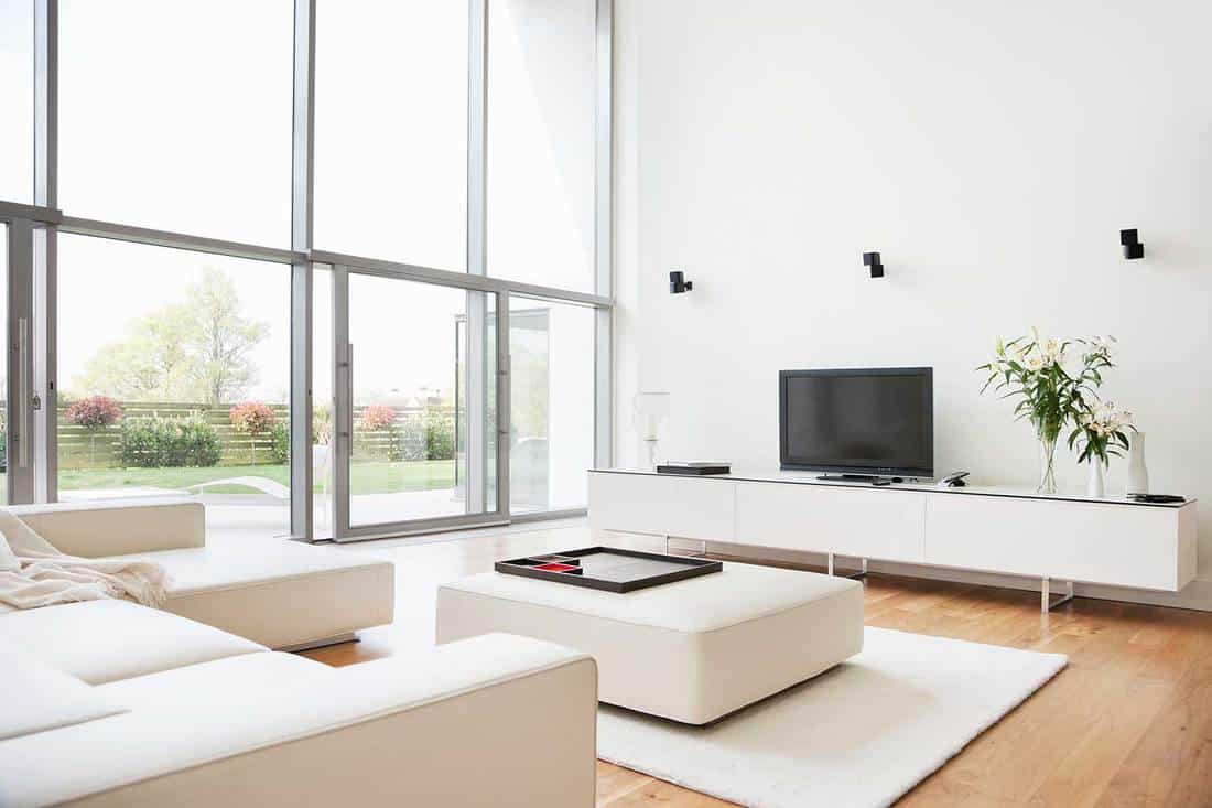 Interior of a bright modern living room with white sofa, white rug and white walls