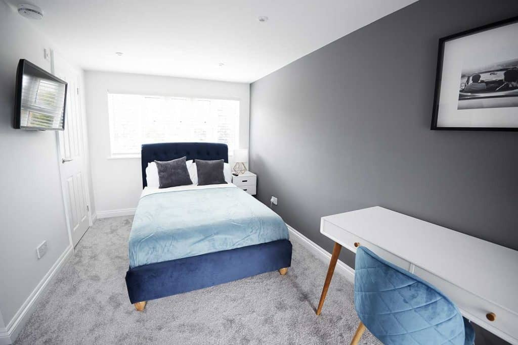 Interior of a hotel bedroom with cozy blue bed, tv, study table and poster on gray wall