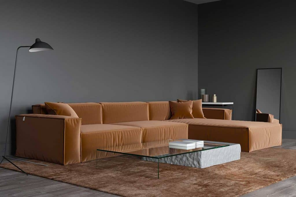 Interior of the living room with large brown sofa and dark gray wall