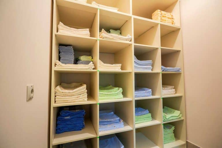 Interior of white plastic cabinet with stacked piles of clean colorful linen on shelves, How to store linens 4 easy solutions