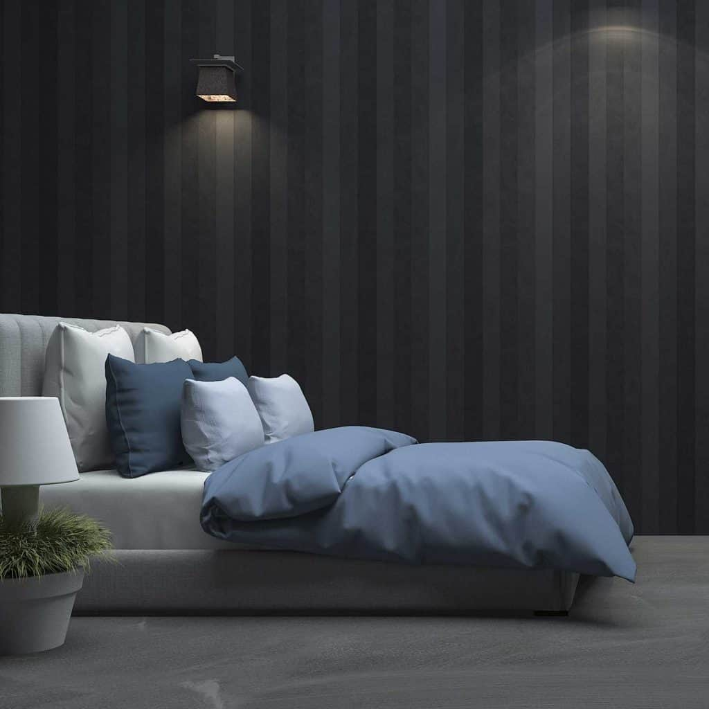 Large bed with blue blanket in a black wood wall bedroom