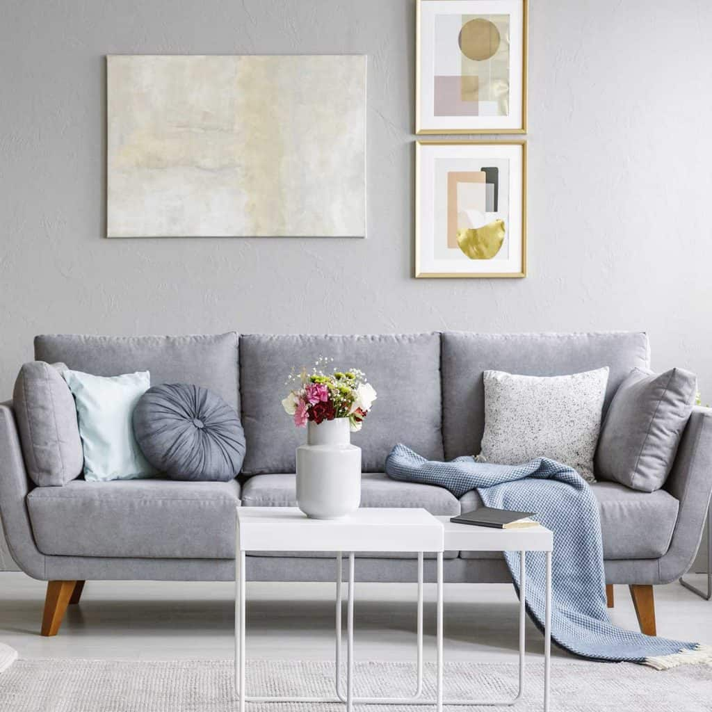 Living room interior gray sofa and flowers on table