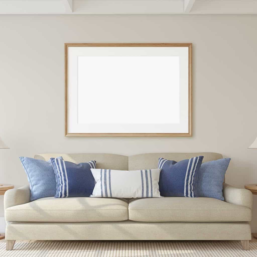 Living room interior with beige sofa, throw pillows and blank poster on wall