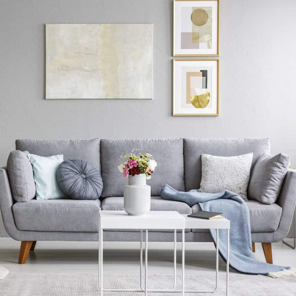 Living room interior with grey sofa and flowers on table