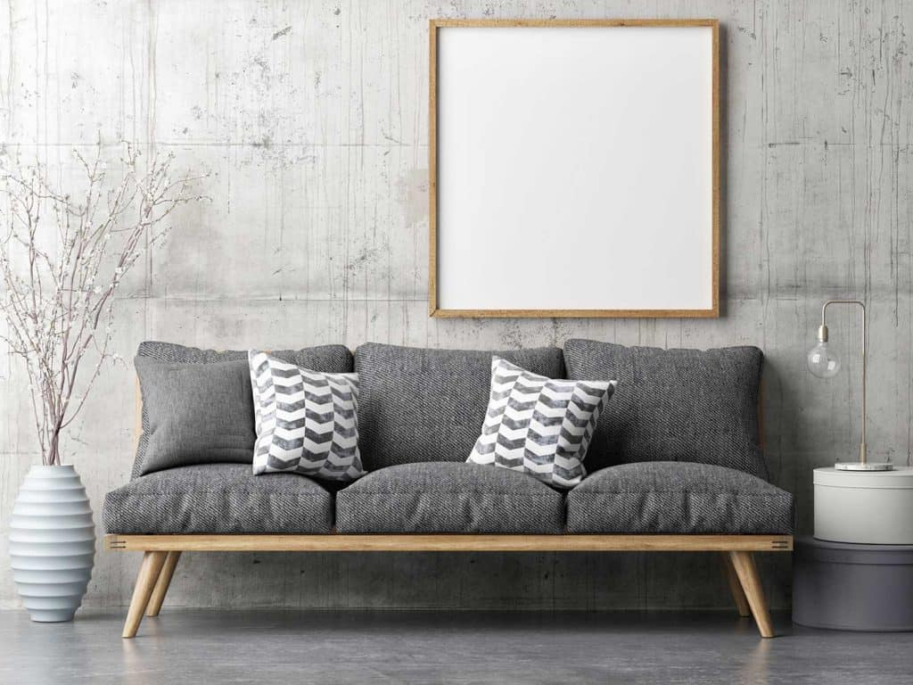 Living room with retro gray sofa and framed blank poster on concrete wall