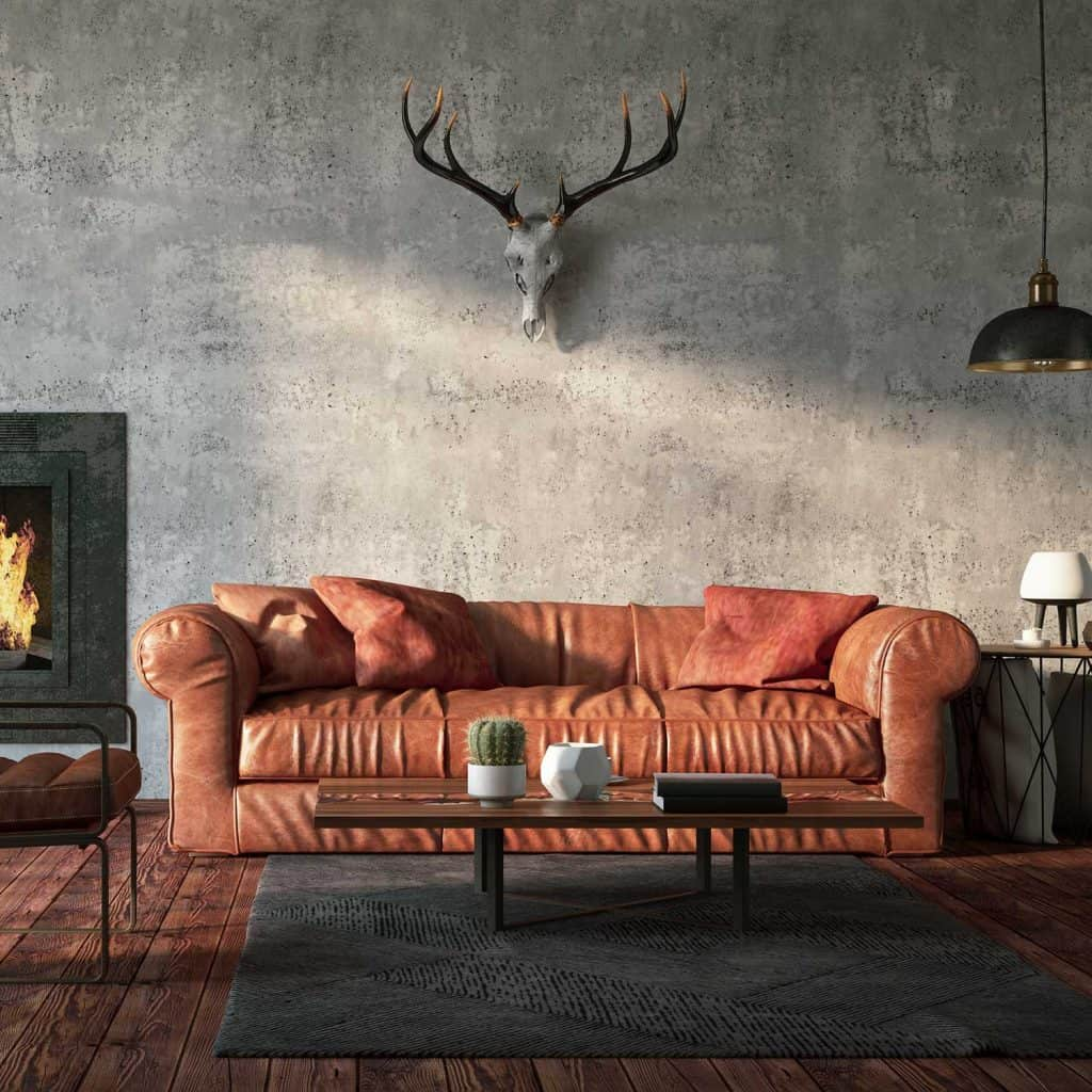 Loft interior with brown leather sofa and deer skull with antler wall decor