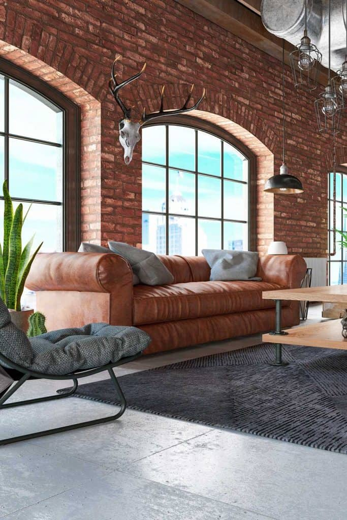 Loft interior with brown leather sofa and furnitures