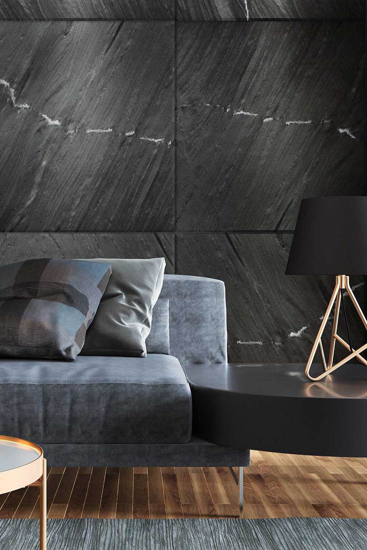 Luxurious apartment living room with natural black stone wall tiles, modern grey sofa and black metal lamp