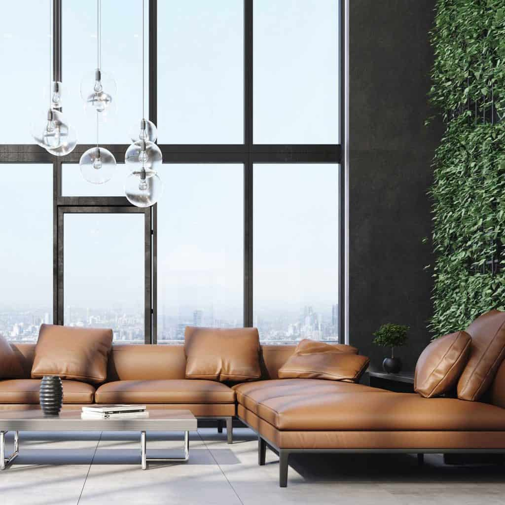 Luxury modern living room interior with brown leather corner sofa, industrial lights and green wall