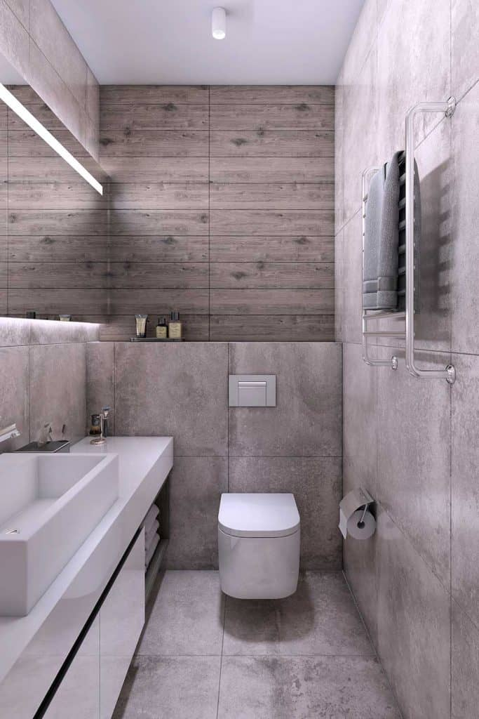 Modern bathroom interior with concrete textured wall, toilet seat, sink and wooden paneling wall in the background
