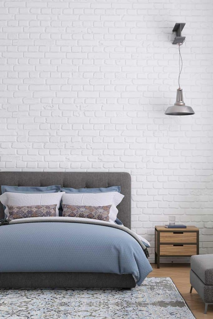 Modern bedroom interior with warm cozy bed, bedside table, white brick wall and wall lamp