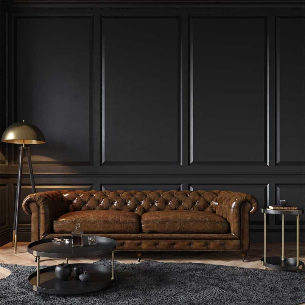 Modern classic black interior with capitone brown leather chester sofa, floor lamp, coffee table, carpet, wood floor and mouldings