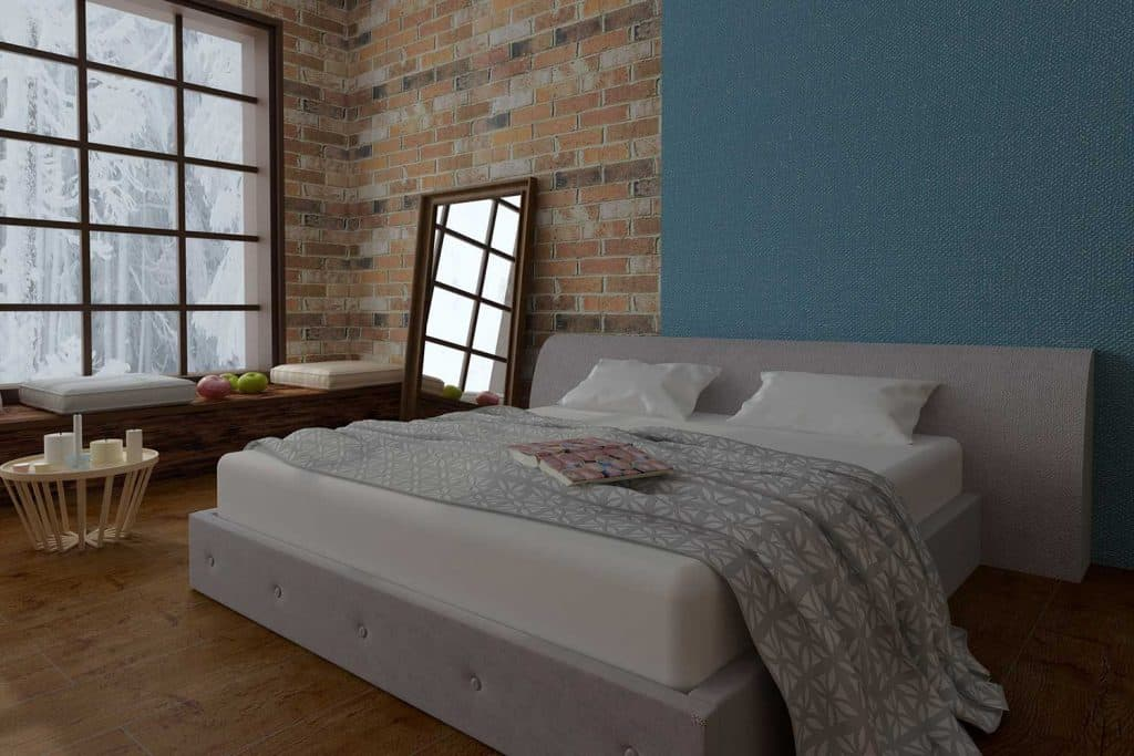 Modern cozy bedroom with brick walls, large windows, mirror, hardwood floor and coffee table with candles
