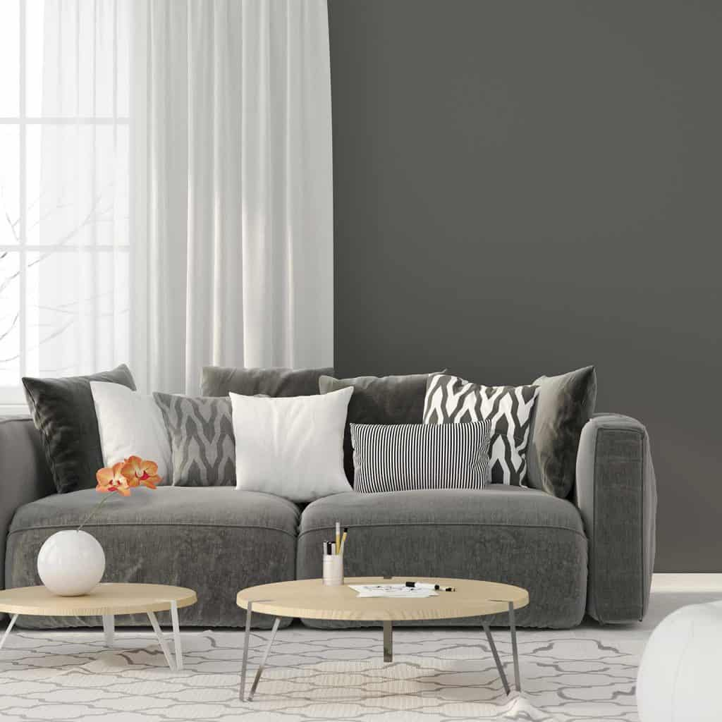 Modern interior living room with a gray sofa and many pillows