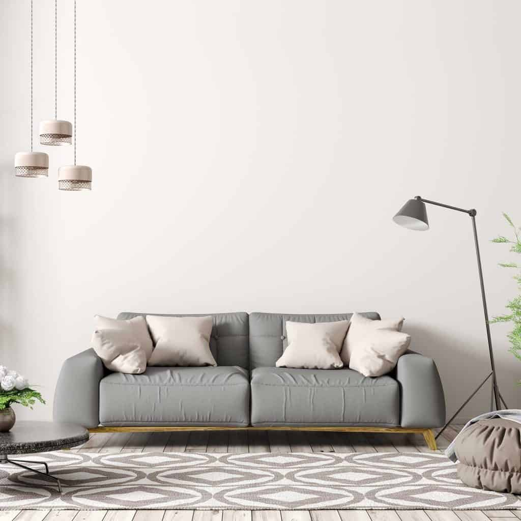 Modern interior of apartment, living room with gray sofa, floor lamp, coffee table and hardwood floor