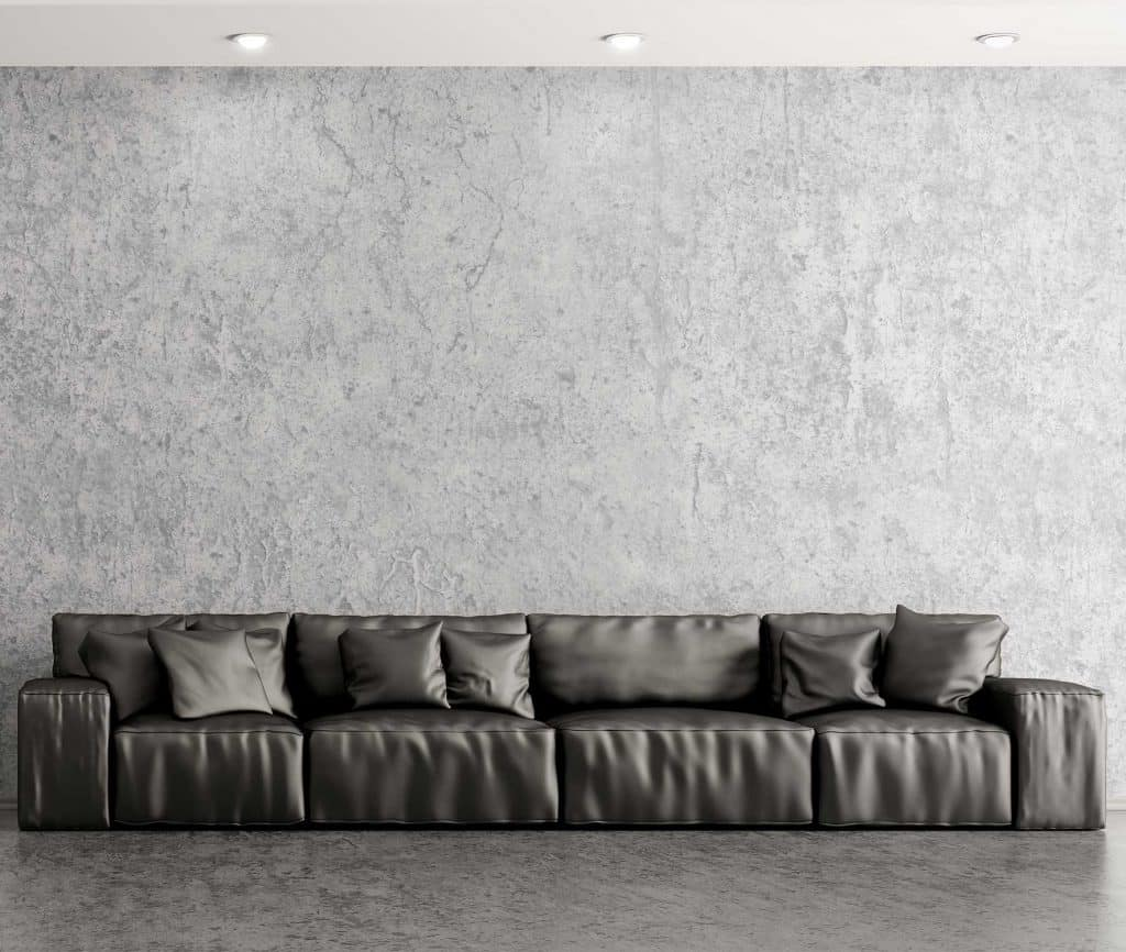 Modern interior of living room with black leather sofa against of concrete wall